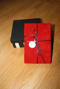 The box, along with the book wrapped in the red velvety paper. It's tied with black ribbon and accented with one of the little pocket watch tags - appropriate, I thought, since Frederick Thiessen, who starts the red-scarf thing, is a clockmaker.